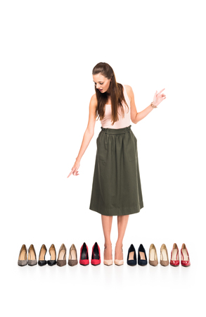 young woman choosing pair of stylish high heels isolated on white