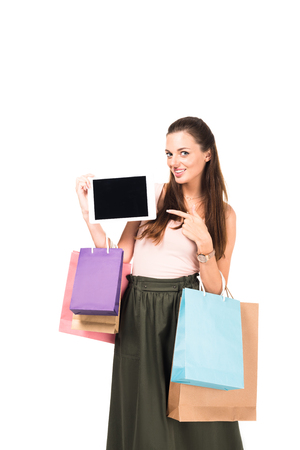 portrait of smiling woman with shopping bags pointing at tablet isolated on white