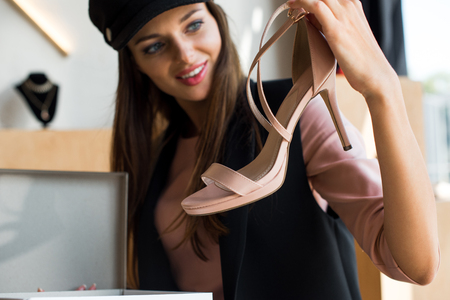 close-up view of happy young woman holding fashionable high heeled shoe Stock Photo