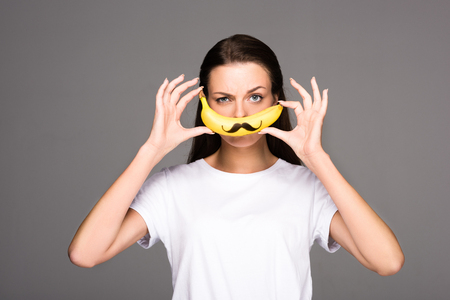 portrait of young woman holding fresh banana with mustache sign isolated on grey 免版税图像