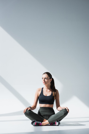 beautiful young sportswoman sitting with crossed legs and looking away on grey
