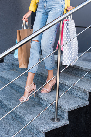 low section of young woman holding shopping bags and going down the stairs Stock Photo