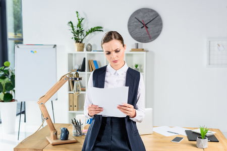 Young businesswoman at her office looking at paperwork and frowning Stock Photo