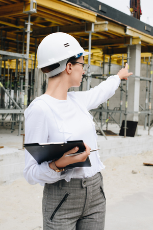 Young engineer in hardhat with clipboard at construction site, pointing her finger at unfinished building 写真素材