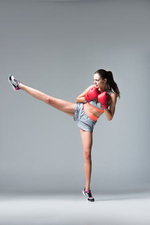 full length view of sporty young woman in boxing gloves fighting on grey Stok Fotoğraf