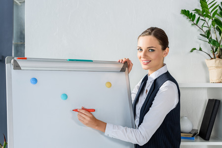 Young businesswoman in office doing a presentation and writing with marker on whiteboard Stock Photo