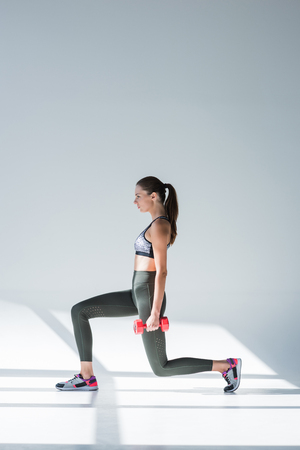 side view of sporty young woman exercising with dumbbell on grey
