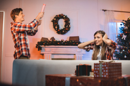 woman covering ears while man letting off party popper, celebrating christmas together at home Stock Photo