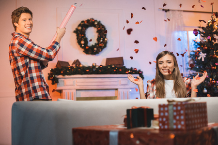 man letting off party popper while celebrating christmas together with girlfriend at home Фото со стока