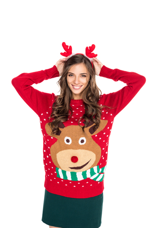 portrait of happy woman in winter festive sweater wearing deer decorative horns isolated on white