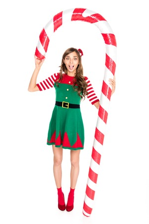 grimace woman in elf costume holding decorative Christmas lollipop isolated on white