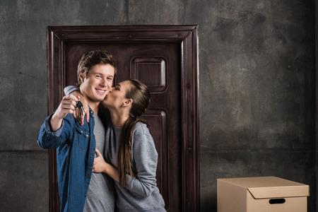happy woman kissing boyfriend with keys from new house in hand Standard-Bild - 102328052