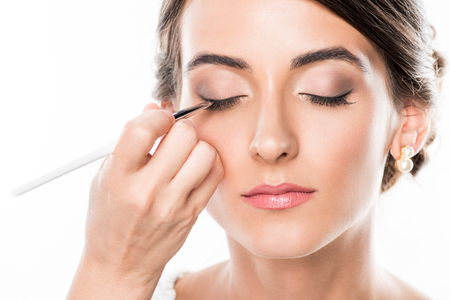 cropped sot of makeup artist drawing eye arrows while makeup model isolated on white Imagens