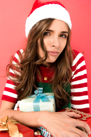 portrait of grimace woman in elf costume and santa hat with christmas presents isolated on red