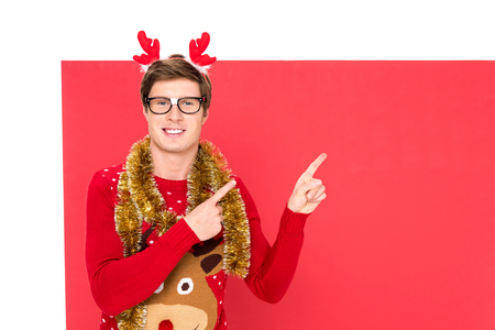 portrait of man with christmas decorations and decorative deer horns on head pointing away