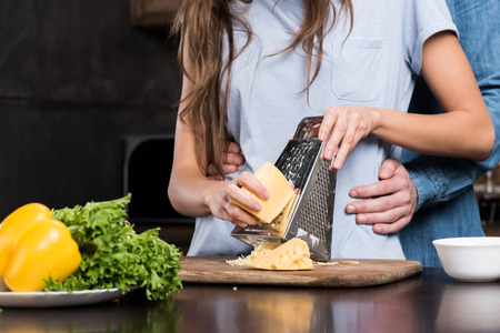 cropped shot of boyfriend hugging girlfriend while she grating cheese for dinner Stock Photo