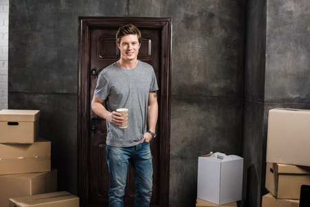 portrait of smiling man with coffee to go in hand standing at new home