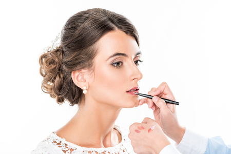 side view of makeup artist applying lipstick on models lips using lip brush isolated on white