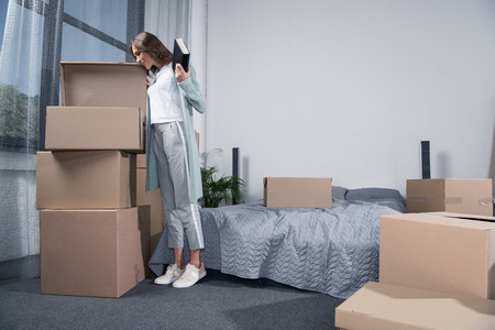 young woman unpacking cardboard boxes at new home, moving home concept