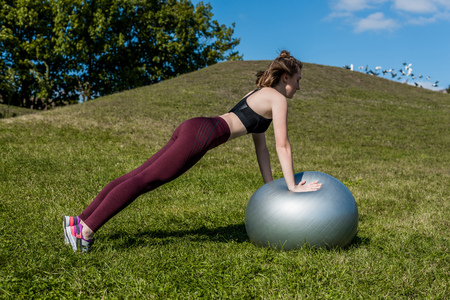 young fit woman working out with fitball outdoors Stock Photo