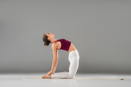 young woman practicing yoga, sitting in Camel exercise, Ustrasana pose