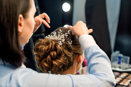 partial view of hairstylist decorating clients hairstyle with beautiful accessory