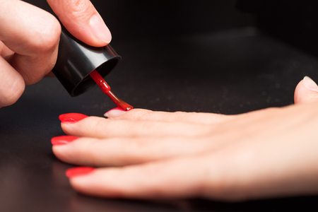 cropped shot of woman receiving manicure by nail beautician