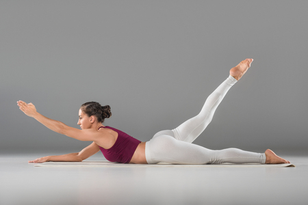 side view of beautiful sporty young woman doing yoga exercise on grey  Stock Photo