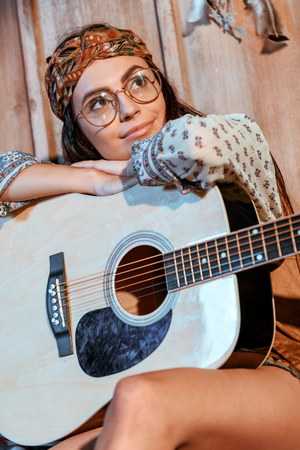 Attractive hippie girl in headband and glasses sitting with a guitar in wooden house