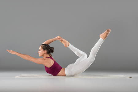 full length view of beautiful sporty young woman doing yoga exercise on grey