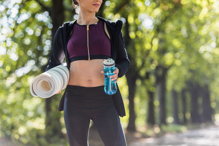 cropped shot of sporty woman with yoga mat and water in park