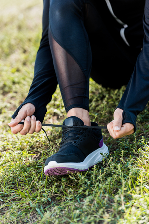 cropped shot of woman lacing sneakers while sitting on grass Stockfoto
