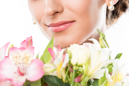 partial view of smiling woman with bouquet of flowers isolated on white