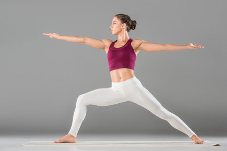sporty young woman practicing yoga warrior pose