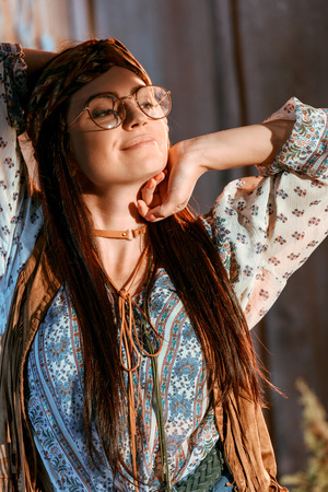 Portrait of beautiful hippie girl stretching in wooden house Stockfoto