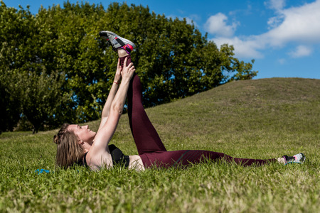 young woman training abs outdoors on grass