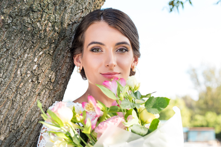 portrait of beautiful woman with bouquet of flowers in park
