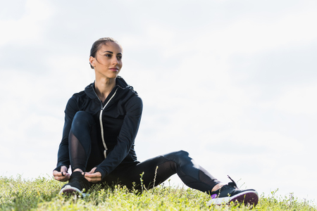 young fit woman lacing sneakers while sitting on grass