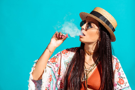 Attractive bohemian girl smoking cigarette and exhaling smoke isolated on turquoise