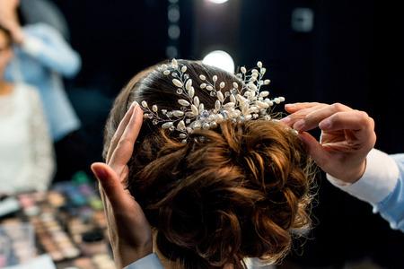 Vue partielle du coiffeur décorant la coiffure des clients avec un bel accessoire