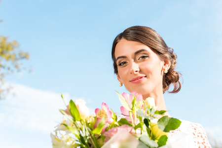 portrait of beautiful woman with bouquet of flowers against blue sky