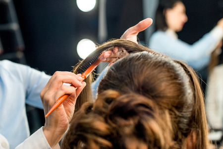partial view of hairdresser doing beautiful hairstyle using hairbrush  Stock Photo