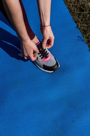 cropped shot of young woman lacing shoe before workout