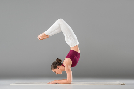 young woman performing yoga headstand with bent legs pose Reklamní fotografie - 102328381
