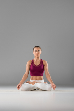 sporty young woman with closed eyes meditating in lotus position on grey Stockfoto