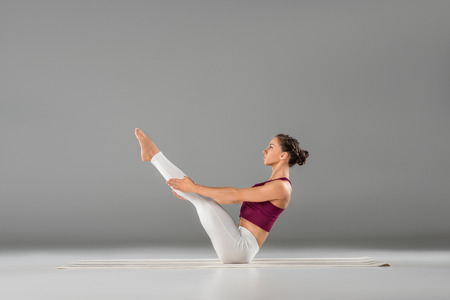 sportive young woman practicing yoga on grey  Stock Photo