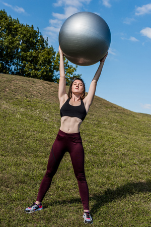 beautiful fit woman holding fitball over head outdoors Stock Photo