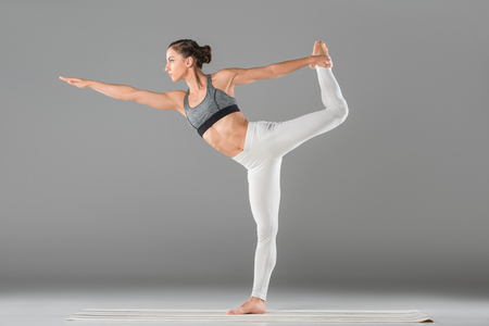 full length view of beautiful young woman in sportswear practicing yoga