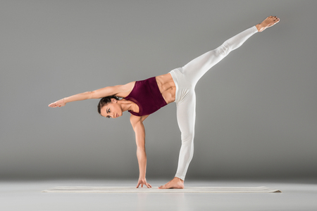 young woman practicing yoga, stretching in Side Plank exercise