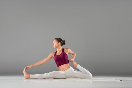 young woman practicing yoga, sitting in Monkey God, Splits exercise, Hanumanasana pose